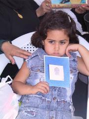 בת אסיר נושאת את תמונת אביה
